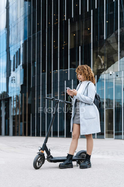 Full body of focus young African American female in blue coat browsing on smartphone while standing on sidewalk with scooter — Stock Photo