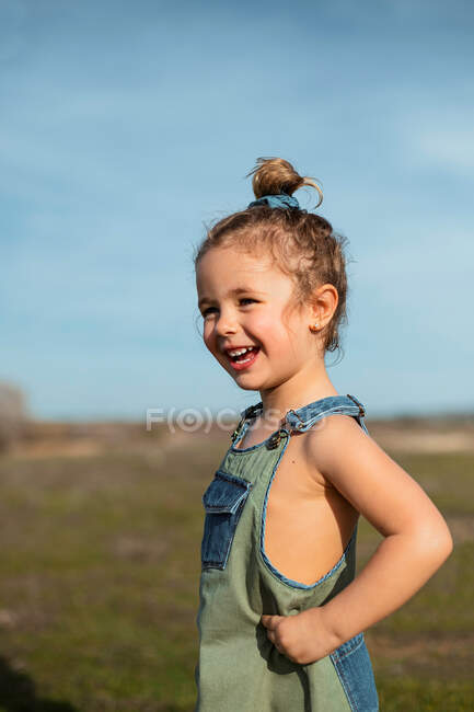 Delighted adorable little girl in overalls standing with hands on waist in meadow and looking away — Stock Photo