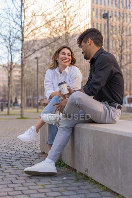 Baixo ângulo de homem e mulher afro-americano elegante com xícaras de café para ir conversar no banco de concreto no centro da cidade — Fotografia de Stock