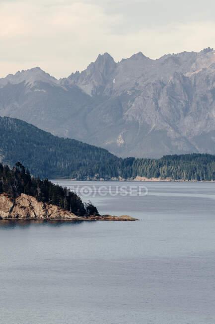 Paesaggio spettacolare di catena montuosa con foresta verde situata vicino al lago calmo con acqua increspata — Foto stock