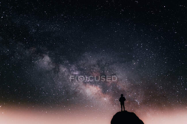 Low angle of silhouette of anonymous tourist standing on cliff against glowing starry sky at night — Stock Photo