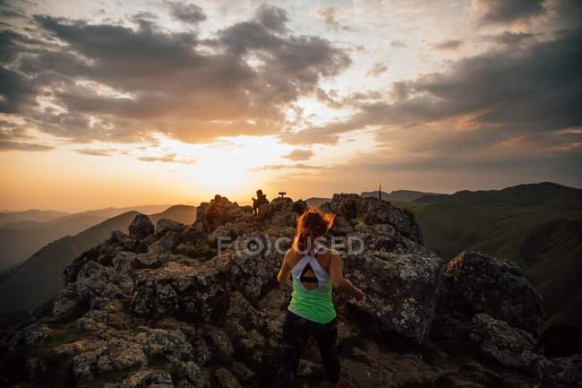Visão traseira da mulher anônima em activewear pulando em pedregulho de alta cumeeira no vale de montanhas sob céu nublado ao pôr do sol — Fotografia de Stock