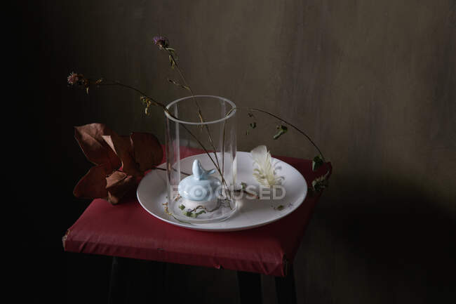 Ваза с декором и выцветшими цветами на круглой пластине с пером на сером фоне — стоковое фото