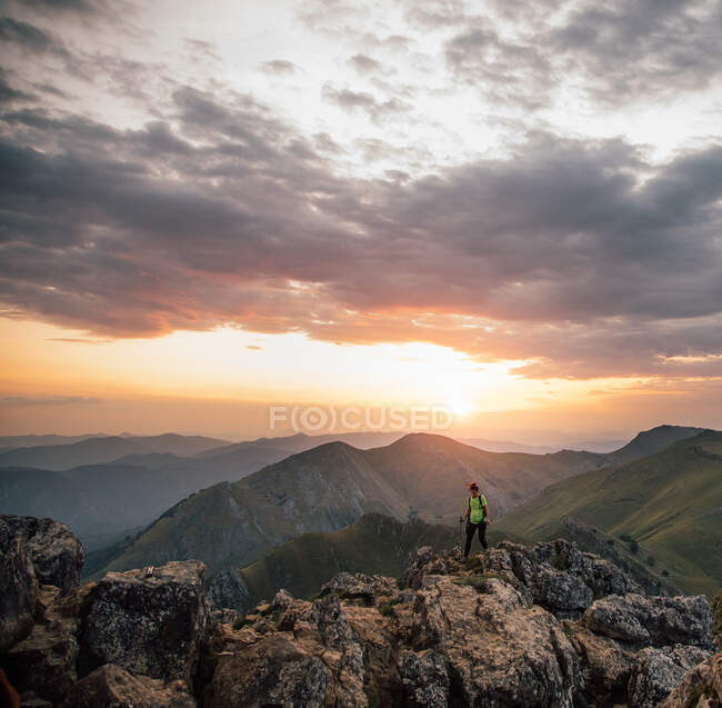 Distant female hiker on high rocky peak of mountain against majestic range under cloudy sky in sunset — Stock Photo
