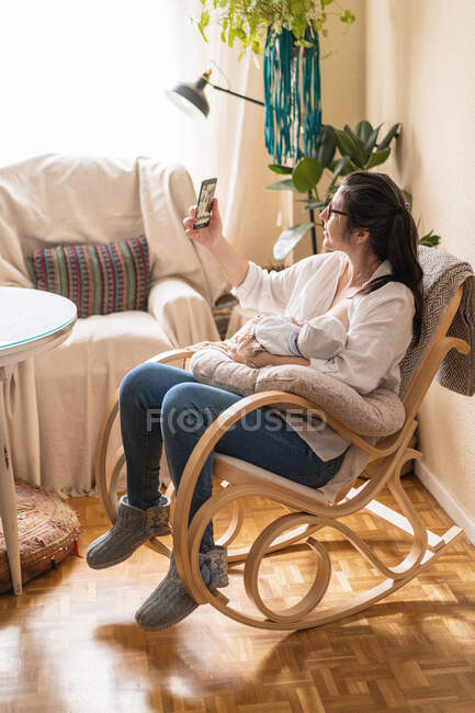 Mom embracing anonymous newborn child and taking self portrait on cellphone in house room on sunny day — Stock Photo