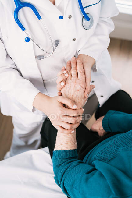 From above crop anonymous doctor speaking with elderly woman while holding hands during examination in hospital - foto de stock