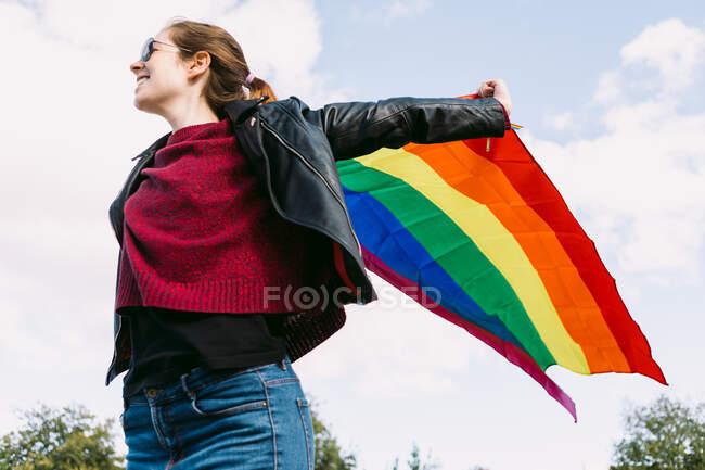 Знизу радісна лесбіянка стоїть на вулиці з ЛГБТ райдужним прапором, що пурхає вітром і озирається на хмарне небо. — стокове фото