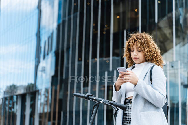 Focus young African American female in blue coat browsing on smartphone while standing on sidewalk with scooter — стоковое фото