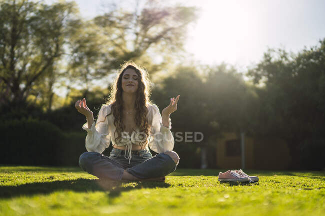 Full body content young female with eyes closed wearing casual wear sitting in Lotus Pose on verdant grassy glade and meditating in sunny park — Stock Photo