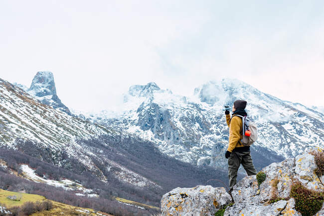 Pieno corpo di turista anonimo con zaino e in abiti caldi in piedi su alta gamma di Cime d'Europa e acqua potabile — Foto stock