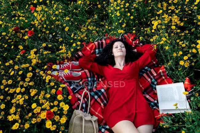 De arriba de la hembra con los ojos cerrados tomando un descanso de la lectura del libro de texto sobre la manta con el bolso entre las margaritas florecientes durante el día primaveral veraniego - foto de stock