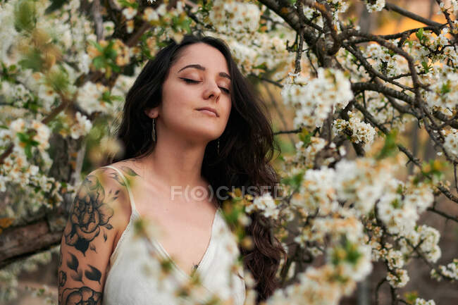 Young female with tattooed arm wearing white dress and standing in flowers of tree with closed eyes — Stock Photo