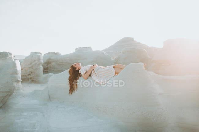 Вид сбоку привлекательная молодая женщина в белом сарафане лежит на грубом каменистом образовании в теплых солнечных лучах — стоковое фото