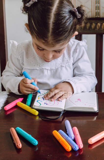 Crop little child sitting at table and drawing with markers in notebook — Stock Photo