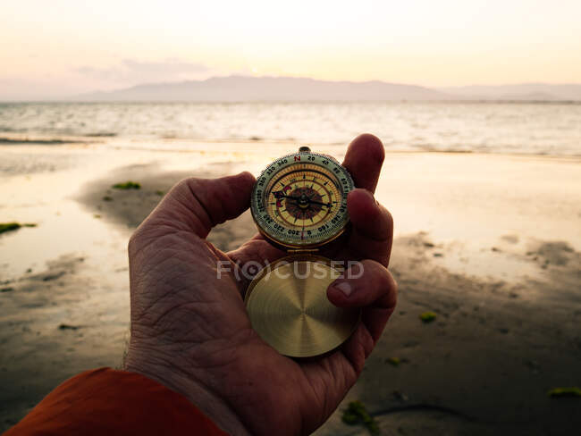 POV crop anonymous adventurer checking route with retro compass while standing on sandy beach near sea at sunset — Foto stock