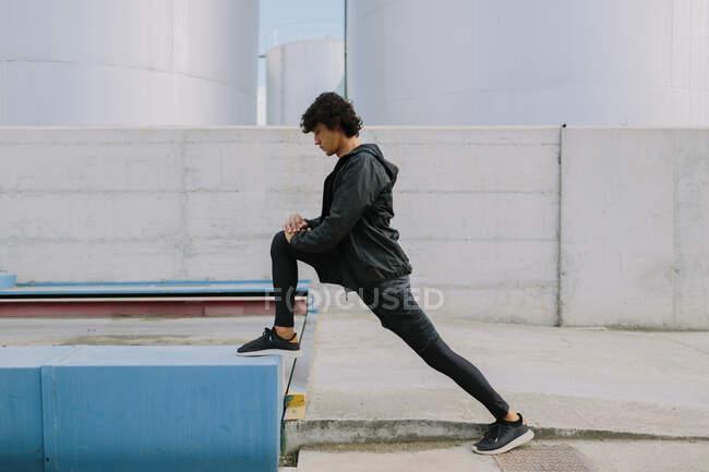 Vista laterale full body maschile in total black abbigliamento sportivo appoggiato con gamba su bock mentre si estende nel quartiere della città industriale — Foto stock