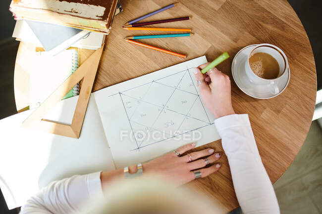 From above of crop unrecognizable female astrologist taking notes on paper with geometric drawing at desk with cup of coffee — Stock Photo