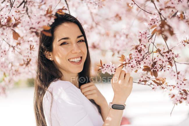 Joven seductora hembra mirando a la cámara bajo el árbol de flores de almendra sobre un fondo borroso - foto de stock