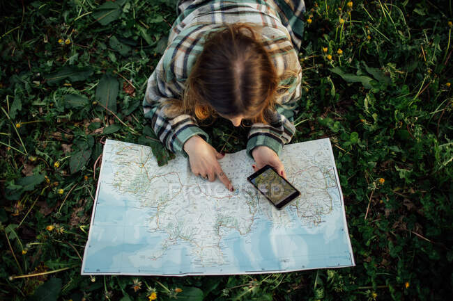 From above back view of unrecognizable female tourist with cellphone watching route map while lying on grass in countryside — Foto stock