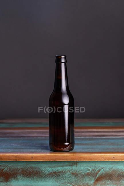 Garrafa de vidro escuro de bebida alcoólica em mesa de madeira pintada em forma quadrada em casa — Fotografia de Stock