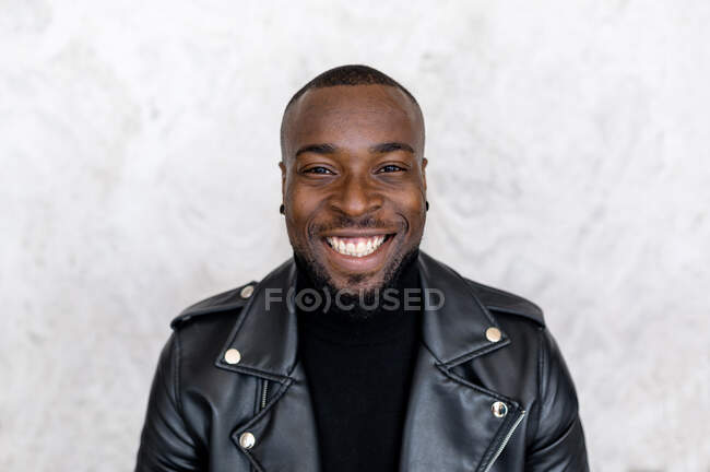 Delighted African American male in stylish leather jacket looking at camera and smiling happily — Stock Photo