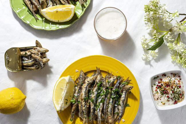 From above of delicious fried anchovies served on plates with lemon and placed on white table with glass of beer — Stock Photo