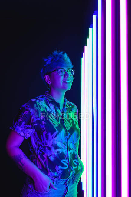 Dreamy female in eyewear and casual clothes with ornament standing with hand in pocket while looking up against artificial lights — Stock Photo