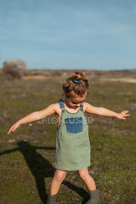 Entzückendes kleines Mädchen in Overalls, das mit ausgestreckten Armen auf der Wiese steht und nach unten schaut — Stockfoto