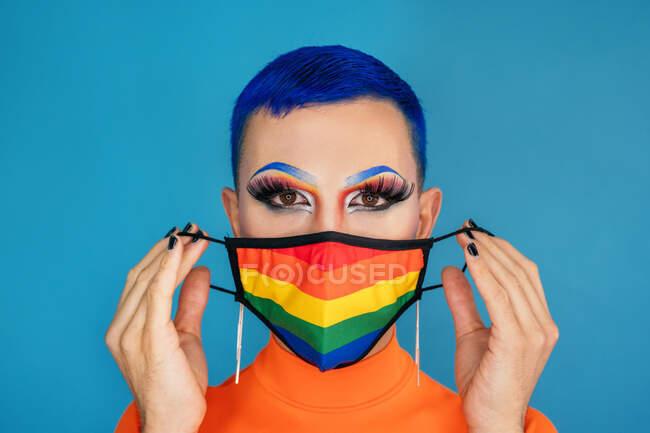 Emotionless drag queen con cabello azul y maquillaje provocativo con máscara protectora en colores de la bandera del arco iris mientras mira a la cámara contra el fondo azul - foto de stock