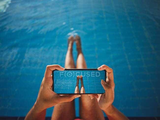 From above of crop anonymous barefoot female taking photo of legs on cellphone over swimming pool with pure water — Stock Photo