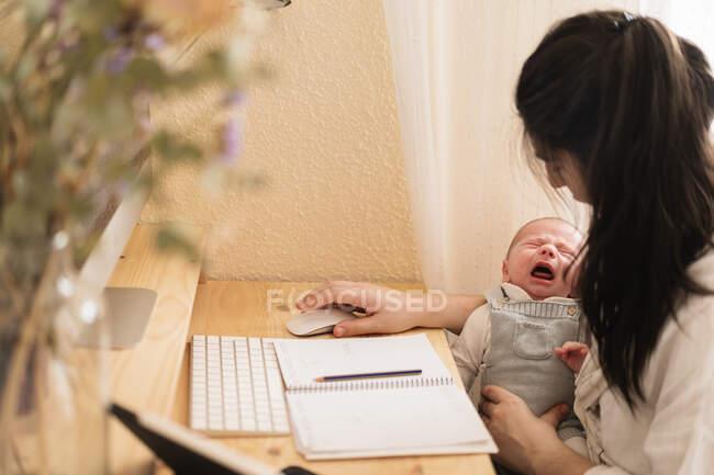 Mãe com a criança chateada sentada à mesa com livro e computador de mesa em casa — Fotografia de Stock