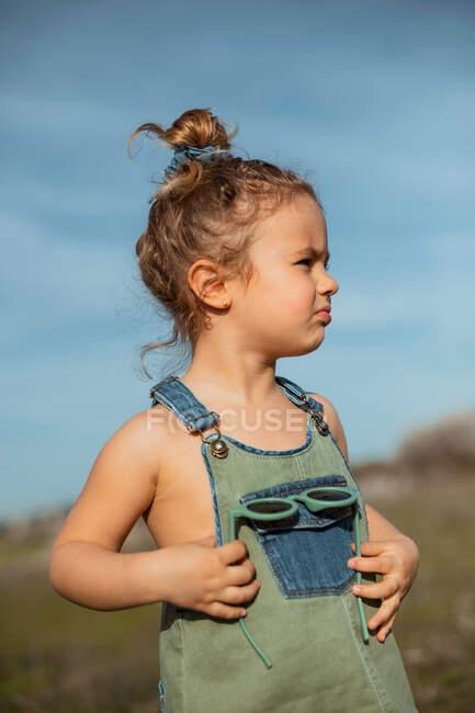 Délicieuse adorable petite fille en salopette debout dans la prairie et regardant loin — Photo de stock