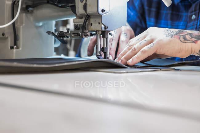 Crop artesano masculino utilizando la máquina de coser, mientras que la creación de tapicería para el asiento de la moto en el taller - foto de stock