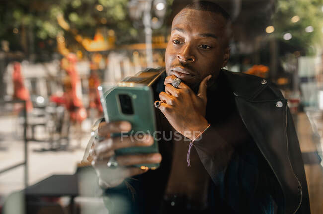 Stylish serious African American male sitting in cafe and surfing Internet on mobile phone - foto de stock