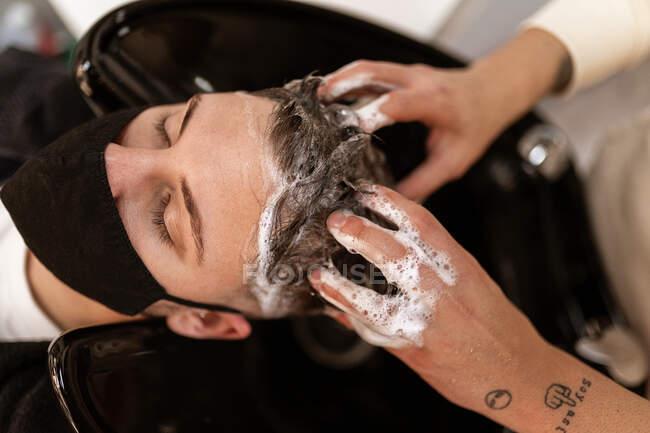 З верху врожаю анонімний перукарня з татуюваннями, які миють волосся людини з шампунем у милиці в перукарні. — стокове фото