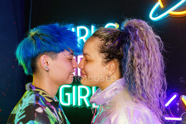 Side view of young lesbian girlfriends touching noses on violet background with eyes closed — Stock Photo
