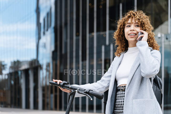 Positive young African American female in blue coat having conversation via smartphone while standing on sidewalk with scooter — Stock Photo