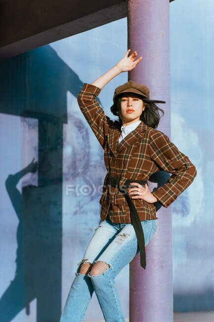 Young Asian woman in checkered jacket and ripped jeans looking at camera while standing with hand on waist in sunlight — Stock Photo