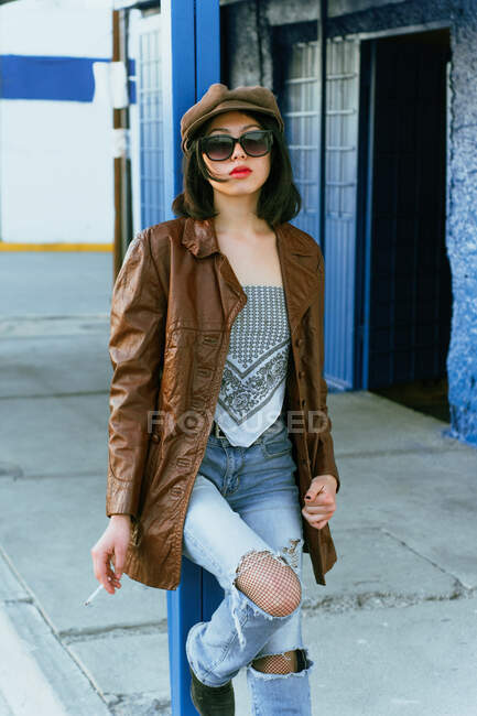 Young ethnic woman in leather jacket and sunglasses standing with hand on hip and looking away on the street — стокове фото