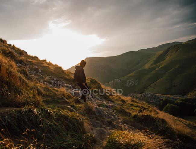 Vista lateral da descida feminina na encosta rochosa da montanha no vale verde com céu nublado ao pôr do sol no fundo — Fotografia de Stock