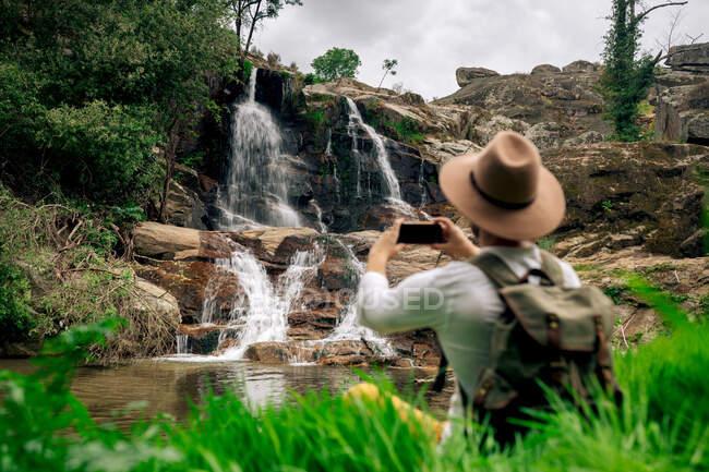 Back view viaggiatore maschile senza volto in abbigliamento casual e cappello scattare foto su smartphone di rapida cascata che cade da formazioni rocciose nella natura verdeggiante — Foto stock