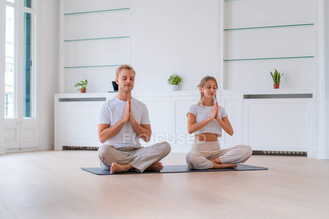 Peaceful couple sitting in Lotus pose with prayer hands while practicing yoga together and meditating with closed eyes — стоковое фото