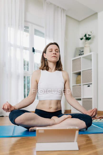 Tranquil female sitting in Lotus pose and listening to meditation on tablet while practicing yoga at home — стоковое фото
