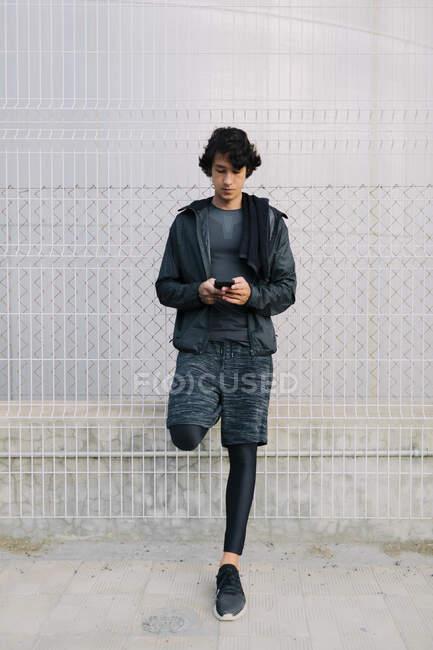 Giovane uomo etnico in abbigliamento sportivo nero appoggiato sulla recinzione di strada e smartphone di navigazione contro l'ambiente urbano — Foto stock
