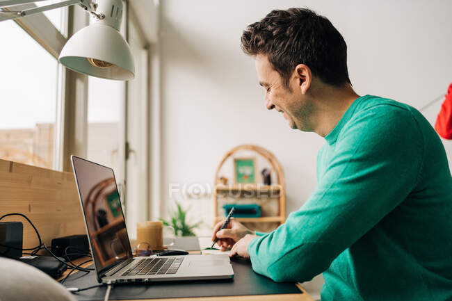 Side view of cheerful male remote worker taking notes against netbook with black screen while working at table in house — Stock Photo