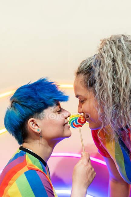 Vista lateral de la joven pareja lesbiana en uso con adorno espectral y deliciosos dulces mirándose entre sí - foto de stock