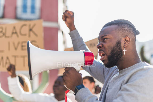 Side view of African American male screaming in megaphone during Black Lives Matter protest in city while standing in crowd of multiethnic demonstrators — Fotografia de Stock
