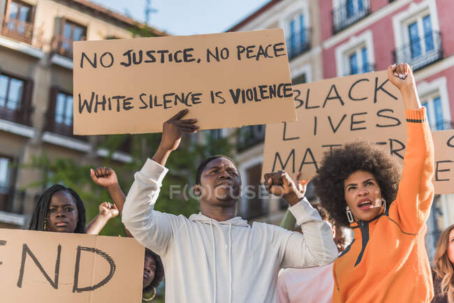 Crowd of multiracial people with Black Lives Matter poster protesting together on city street against racial discrimination — Fotografia de Stock