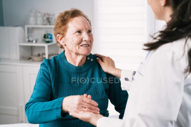 Crop médico anónimo hablando con una alegre anciana mientras se toma de la mano y se mira durante el examen en el hospital - foto de stock