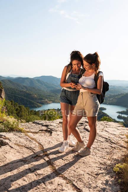 Felice giovani viaggiatori femminili in abiti estivi utilizzando smartphone insieme mentre in piedi su un lussureggiante terreno collinare soleggiato — Foto stock